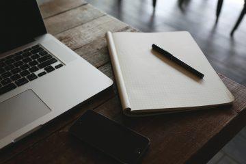 Tisch auf dem ein Laptop, ein Handy und ein Block mit Stift liegen